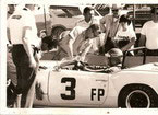 Jim (in cowboy hat) and my mother Lola (in triumph shirt) look on as Dad waits for the go ahead to leave the pits, Riverside 1969.